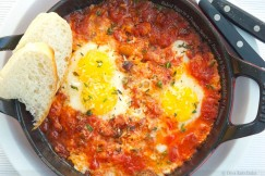 Baked Eggs in a Tomato Sauce with Pancetta and Thyme Sprinkled with Parmesan