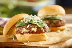 Blue Cheese Stuffed Sliders with Spinach, Crumbled Blue Cheese and 1000 Island on a Brioche Bun