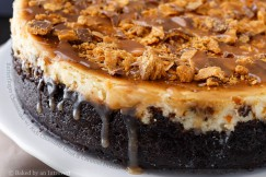 Butterfinger Cheesecake with Rich Chocolate Crust and Caramel Drizzle