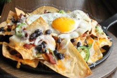 Cheesy Breakfast Nachos Loaded with Bacon, Black Beans, Jalapenos, Shallots and a Fried Egg