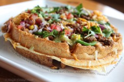 Crispy Waffle Nachos Loaded with Bacon, Ground Beef, Cheese, Jalapenos, Garlic, Onions, Cilantro and Hot Sauce