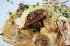 Duck Confit Ravioli with Mushroom Cream Sauce and Micro Kale