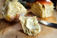 Fluffy Sage and Apple Cider Dinner Rolls Smeared with Butter