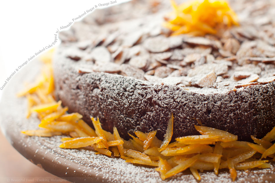 Grand Marnier and Orange Juice Soaked Cake Topped with Almonds, Powdered Sugar and Orange Zest