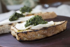 Grilled Crusty Bread Rubbed with Garlic and Topped with Fresh Mozzarella and Kale Pesto