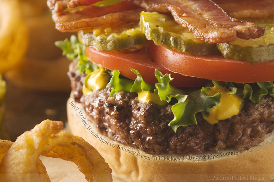 Juicy Grilled Hamburger with Smokey Bacon, Dill Pickles, Lettuce and Ripe Tomato