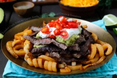Loaded Curly Fries w/ Carne Asada, Guacamole, Sour Cream and Tomatoes