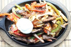 Loaded Fajita Cheese Fries with Marinated Steak, Peppers, Onions, Salsa and Sour Cream