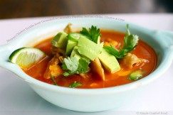 Mexican Chicken Tortilla Soup Garnished with Avocado, Cheddar, Serrano Chiles, Cilantro and Lime