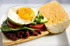 Mexican Chorizo Torta with Fried Egg, Sriracha Aioli, Avocado, Jalapeno, Cilantro, Tomato and Lettuce