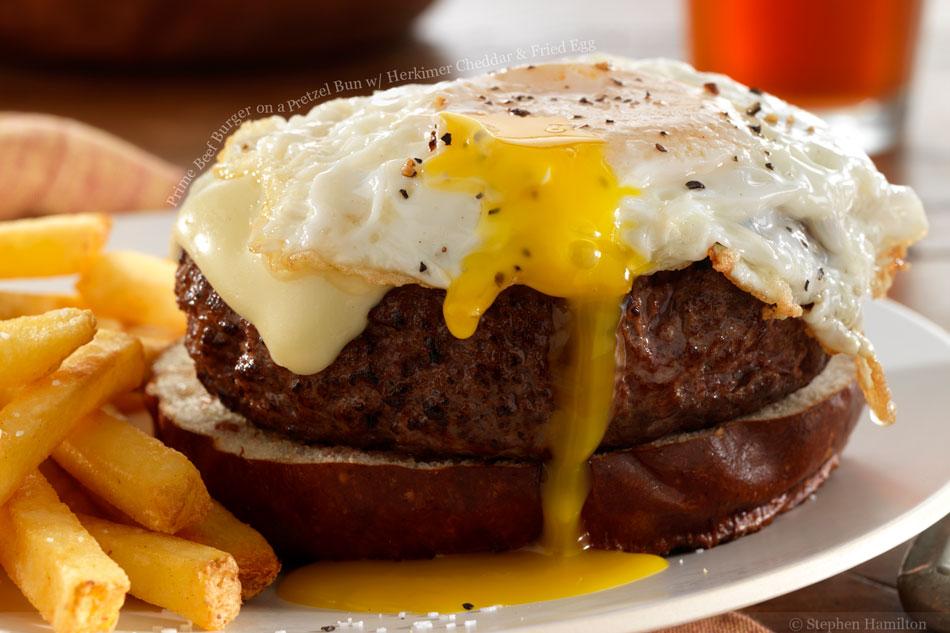 Prime Beef Burger on a Pretzel Bun with Herkimer Cheddar and Fried Egg