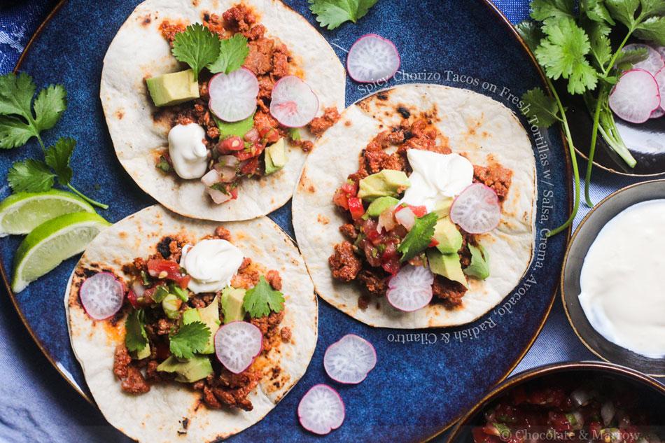 Spicy Chorizo Tacos on Fresh Tortillas with Salsa, Crema, Avocado, Radish and Cilantro