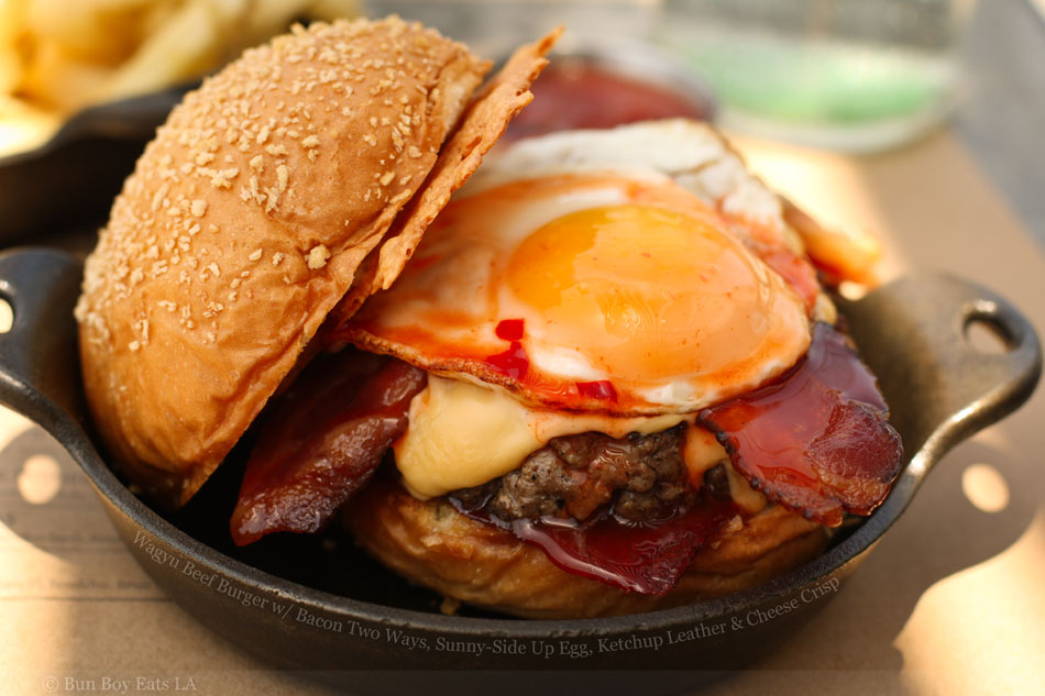 Wagyu Beef Burger with Bacon Two Ways, Sunny-Side Up Egg, Ketchup Leather and Cheese Crisp
